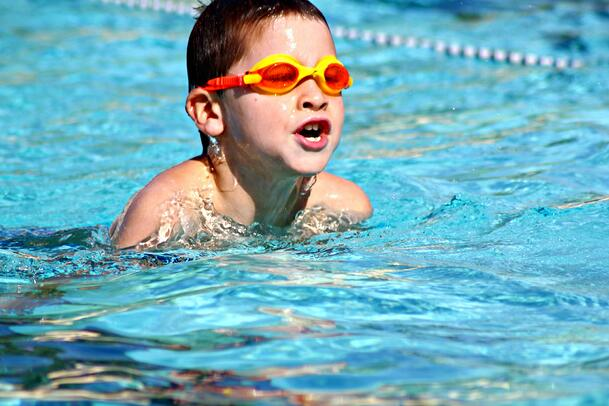 Boy Swimming Safely in Pool